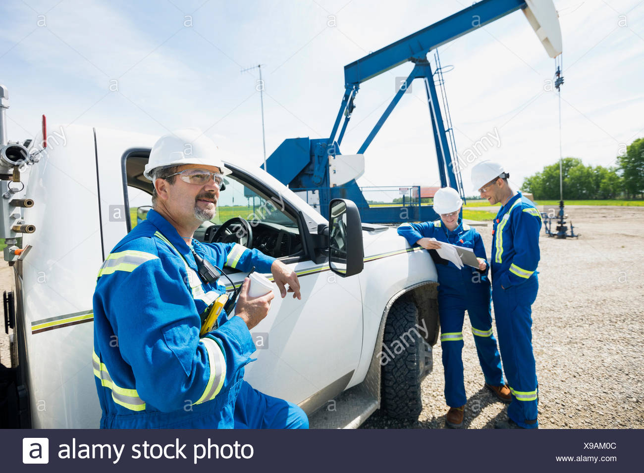 Workers at truck near oil well - Stock Image