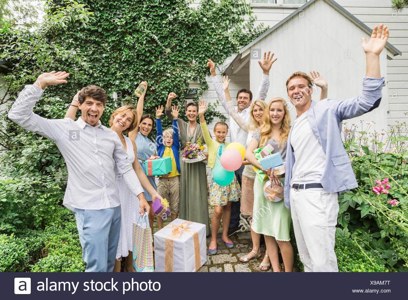 Portrait of three generation family with birthday gifts smiling and waving - Stock Image