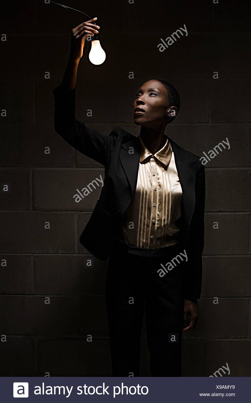 Businesswoman holding lightbulb - Stock Image