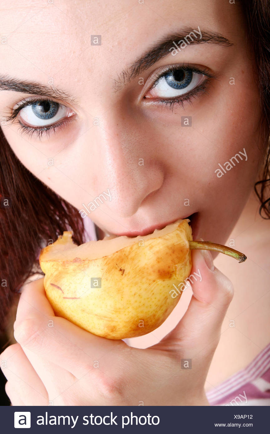 young woman with auburn curls is eating a pear - Stock Image