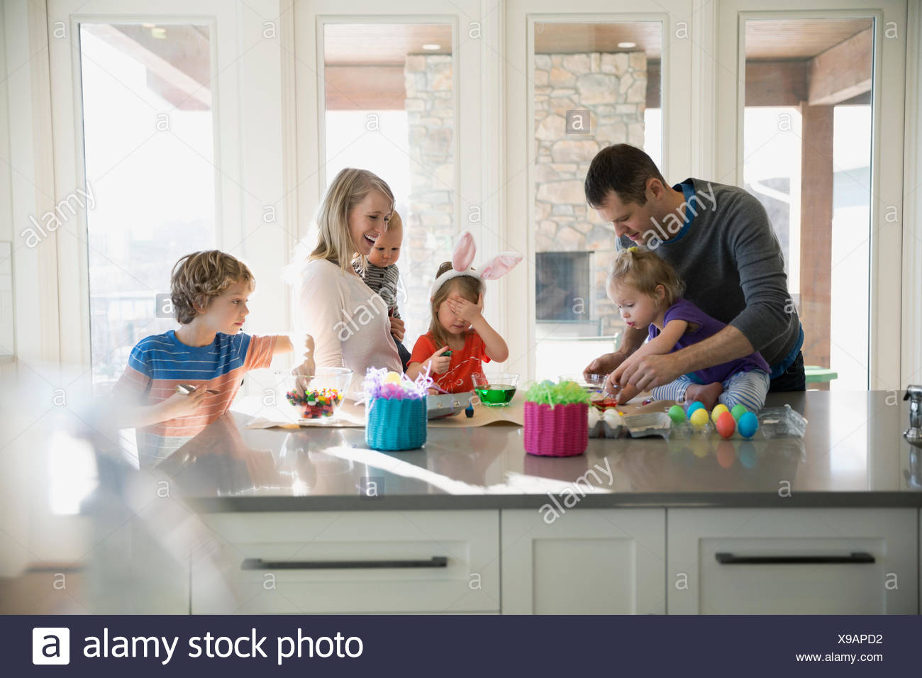 Family coloring Easter eggs in kitchen - Stock Image
