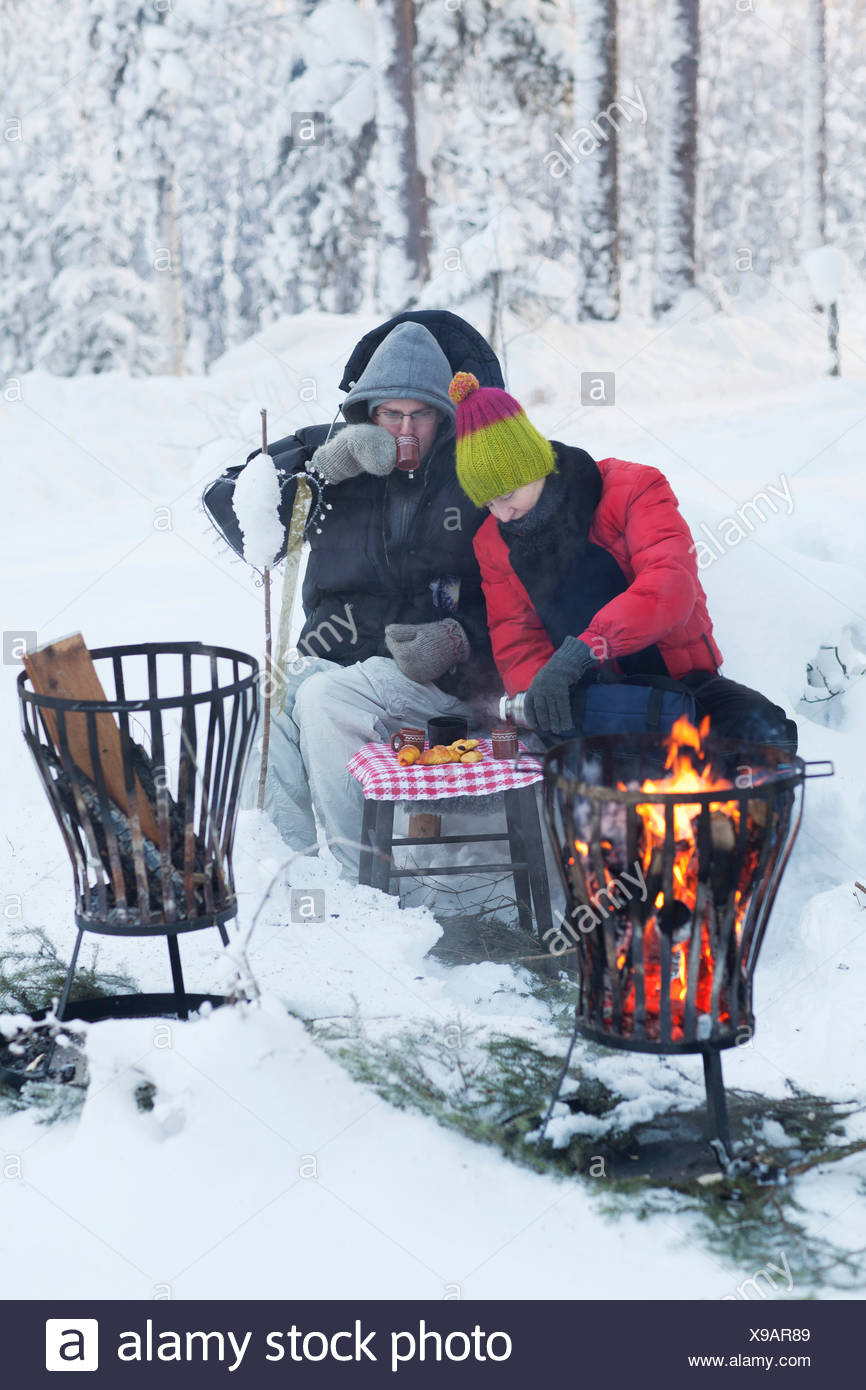 Couple picnicking by fire in snow - Stock Image