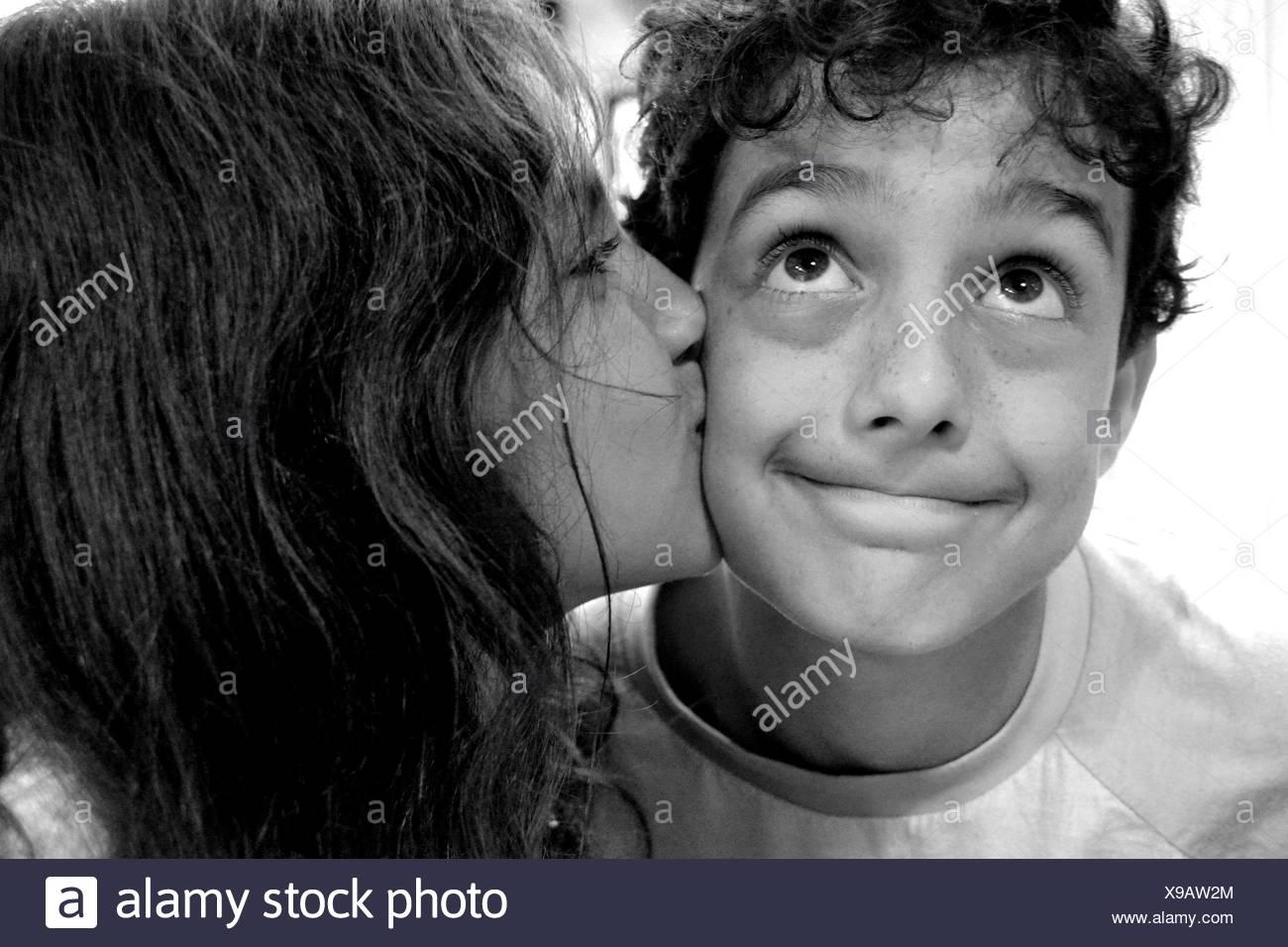 Girl kissing boy on the cheek - Stock Image