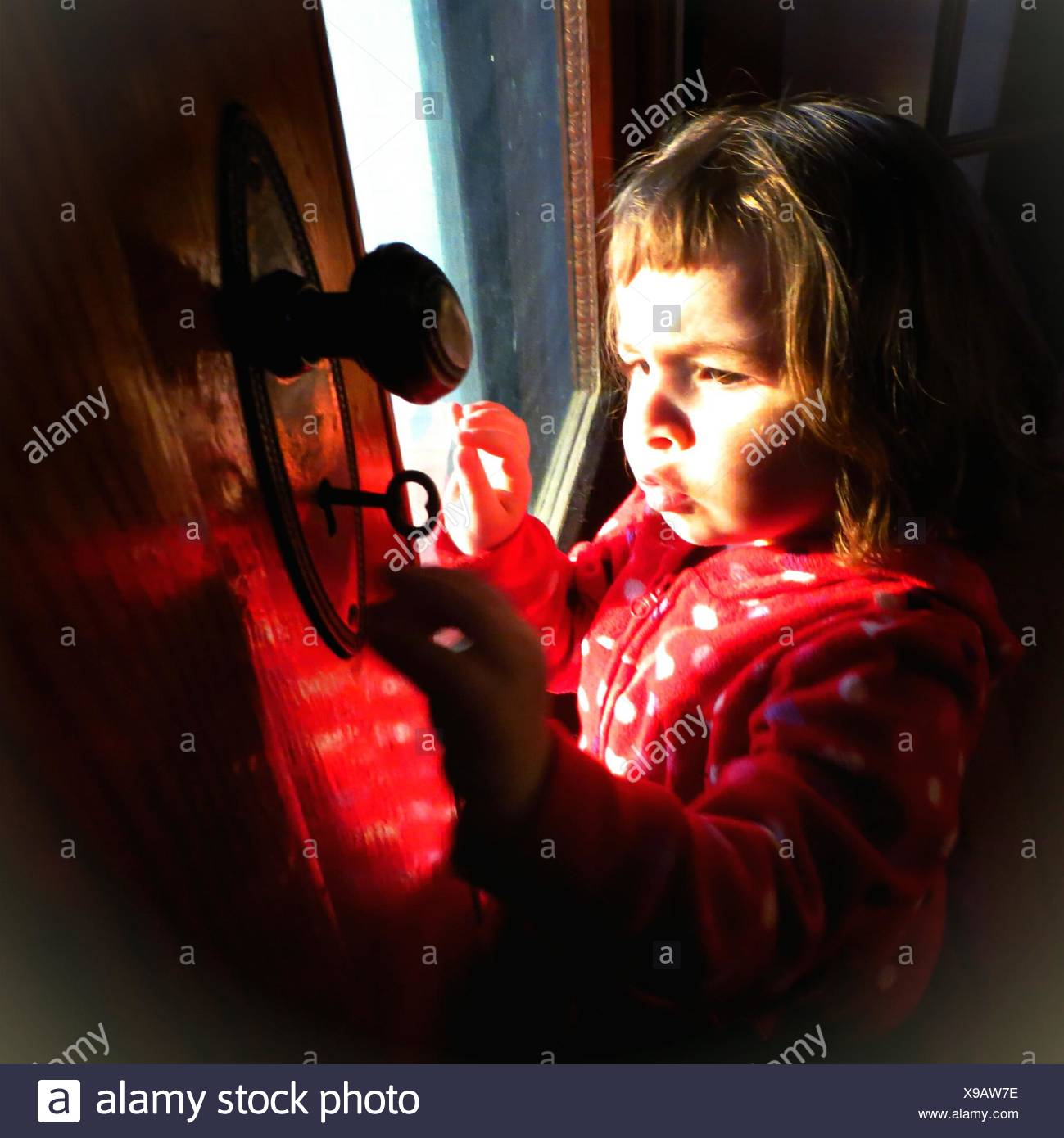 Cute Girl Opening Door With Keys At Home - Stock Image