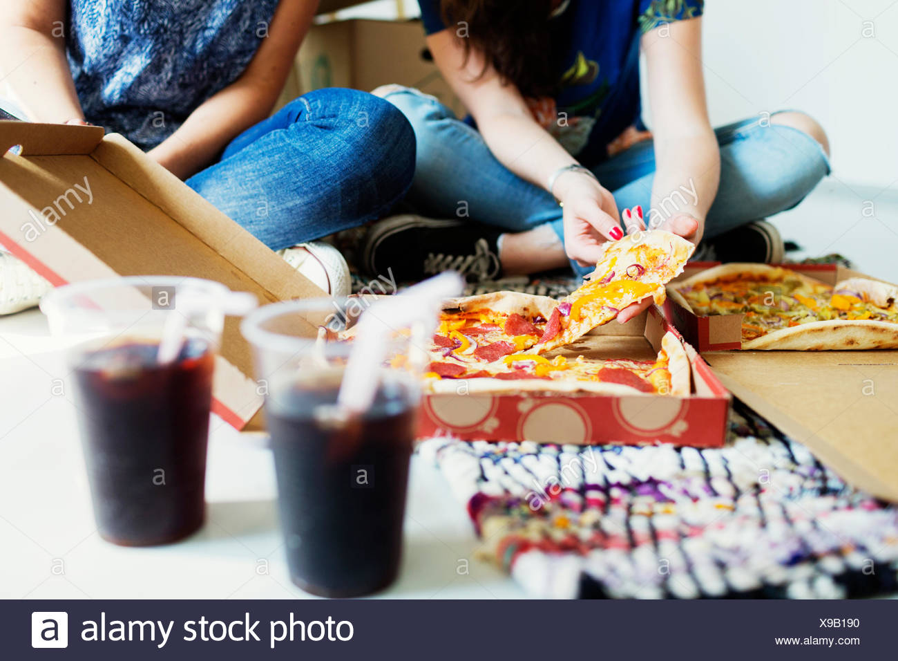 Low section of female friends having pizza in new house - Stock Image