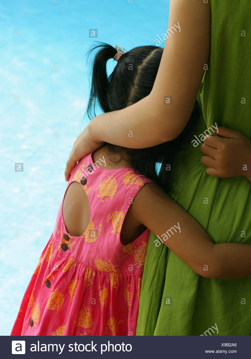 Mid section view of a woman hugging her daughter at the poolside - Stock Image