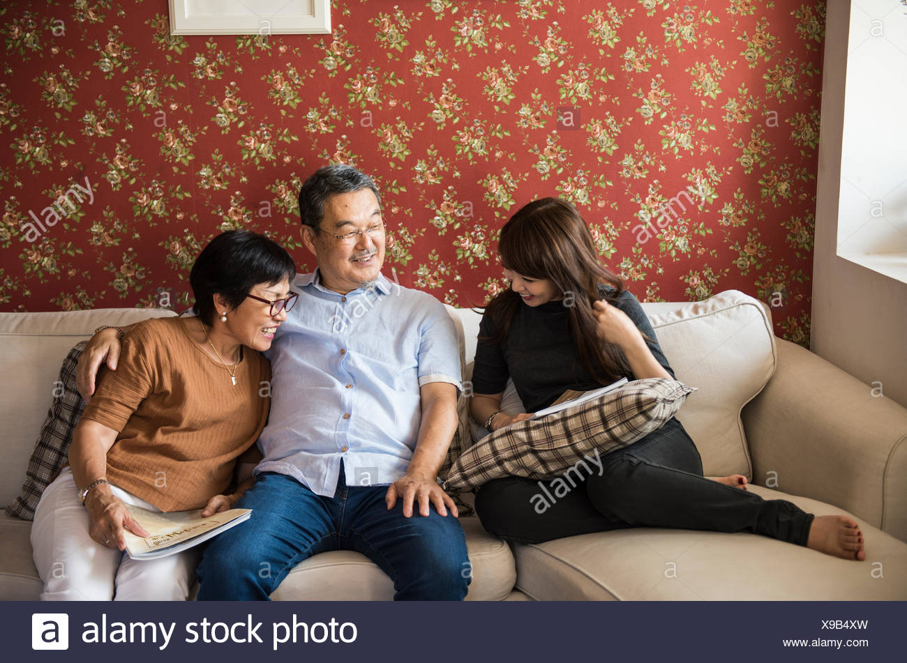 Asian family having fun in the living room together - Stock Image