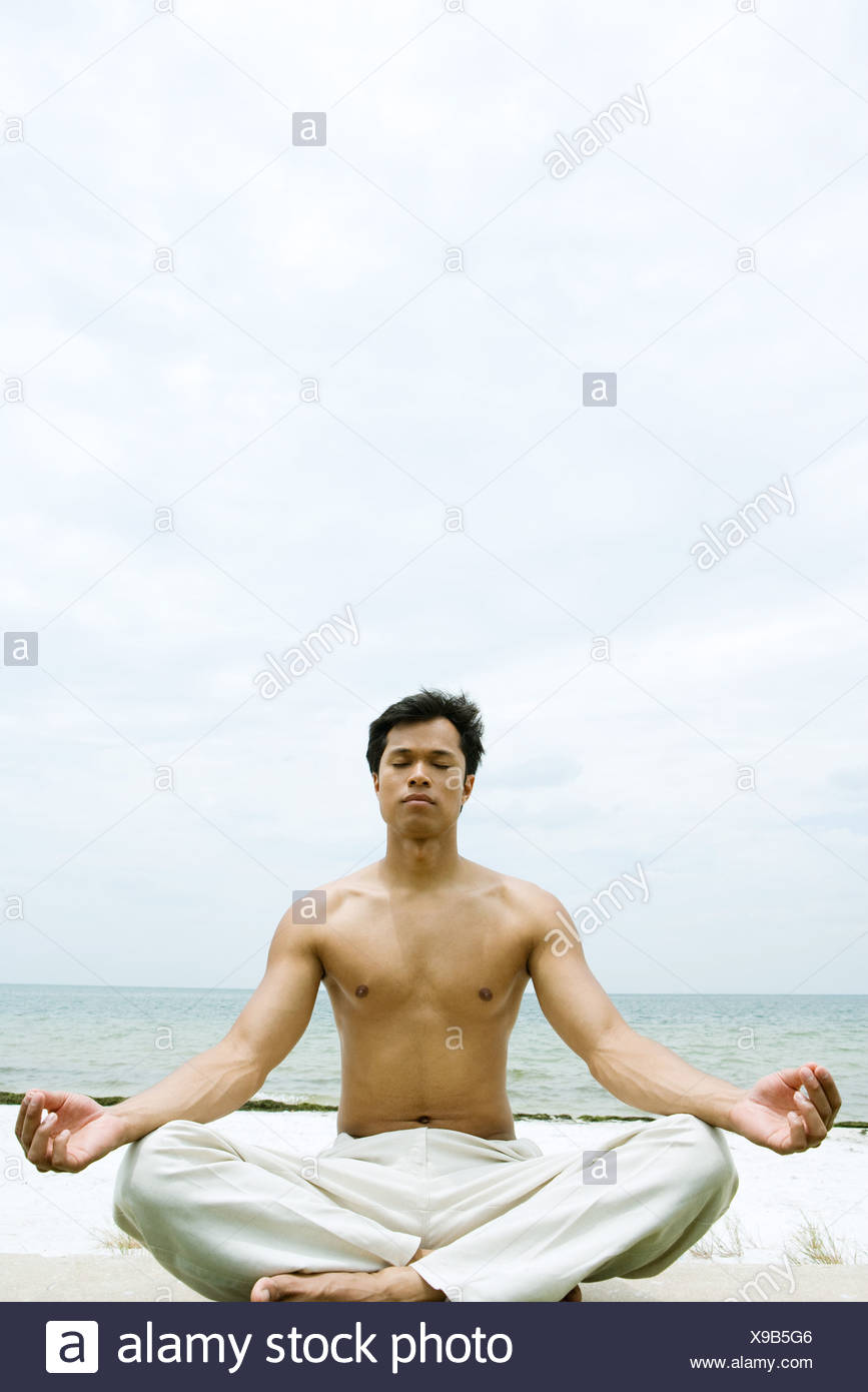 Barechested man sitting in lotus position, ocean in background - Stock Image