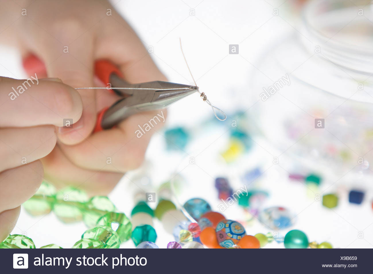 A young girl making a bead necklace with pliers and wire thread, close-up of hands - Stock Image