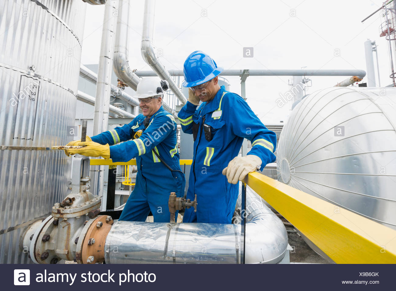 Male workers checking equipment at gas plant - Stock Image