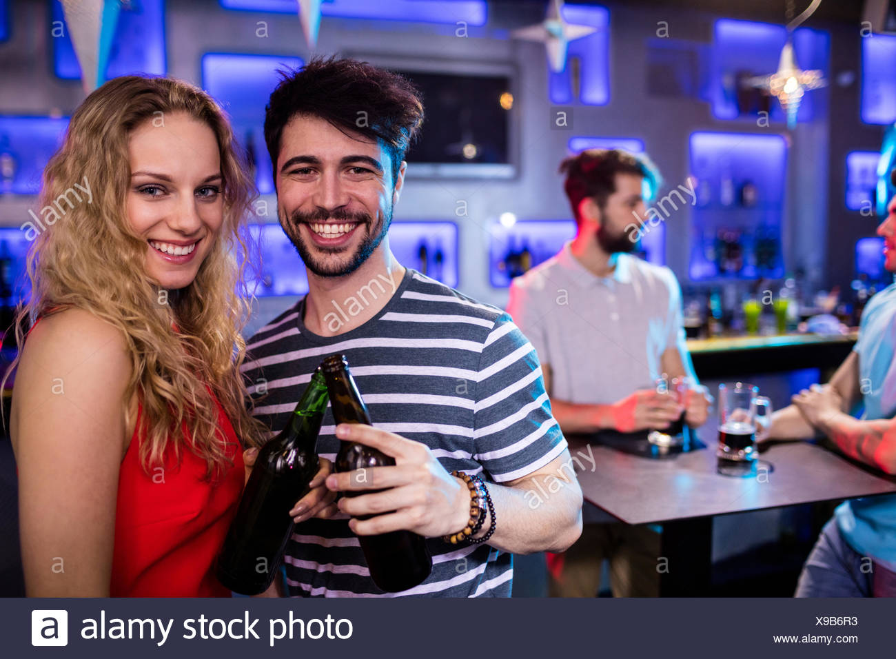Happy couple toasting a beer bottles - Stock Image