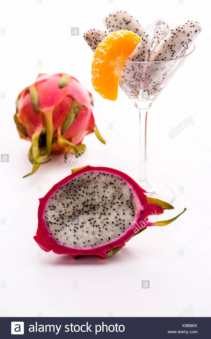 A longitudinal section of a pitaya. Its white pulp is covered with a vibrant violet skin. Its flavor is in harmony with the aroma of the mandarine. - Stock Image