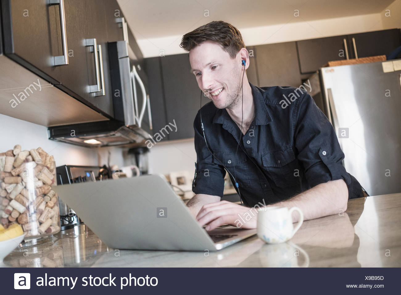Man smiling while working on laptop computer in kitchen - Stock Image