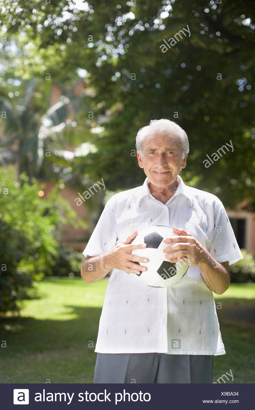 Senior man outdoors holding soccer ball and smiling - Stock Image