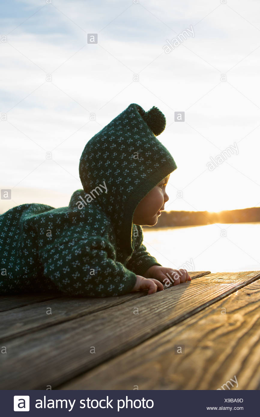 Baby girl crawling on jetty - Stock Image