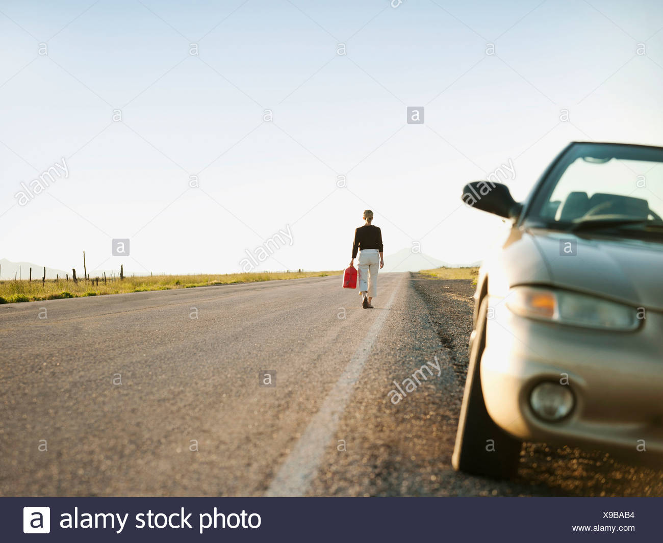 USA, Utah, Kanosh, Woman carrying canister walking along empty road, her car parked on roadside - Stock Image
