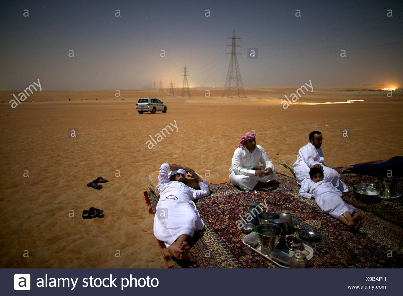 Al Mazrouei Bedouins relish an evening in their ever changing desert. - Stock Image