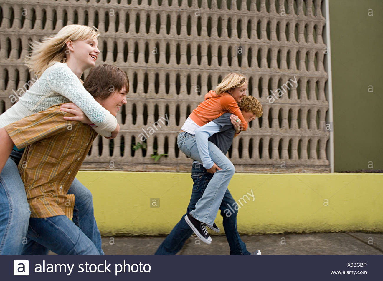 Four teenagers running piggy back races Stock Photo