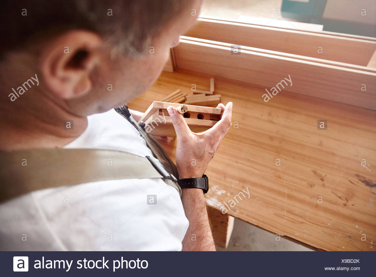 Over shoulder view of carpenter inserting wooden dowel at workbench - Stock Image