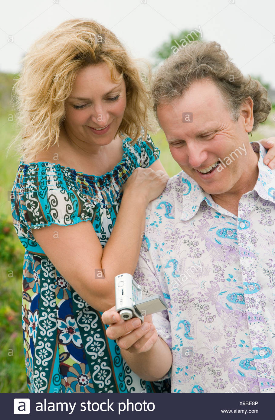 Mature couple looking at a home video camera - Stock Image