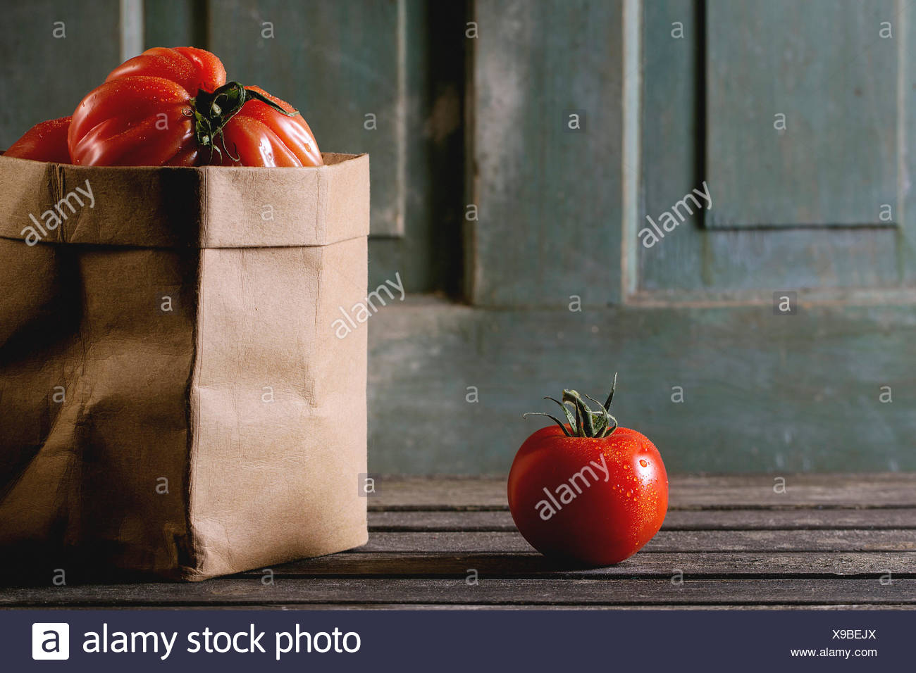 One and heap of big red tomatoes RAF in paper bag over old wooden table. Dark rustic atmosphere - Stock Image
