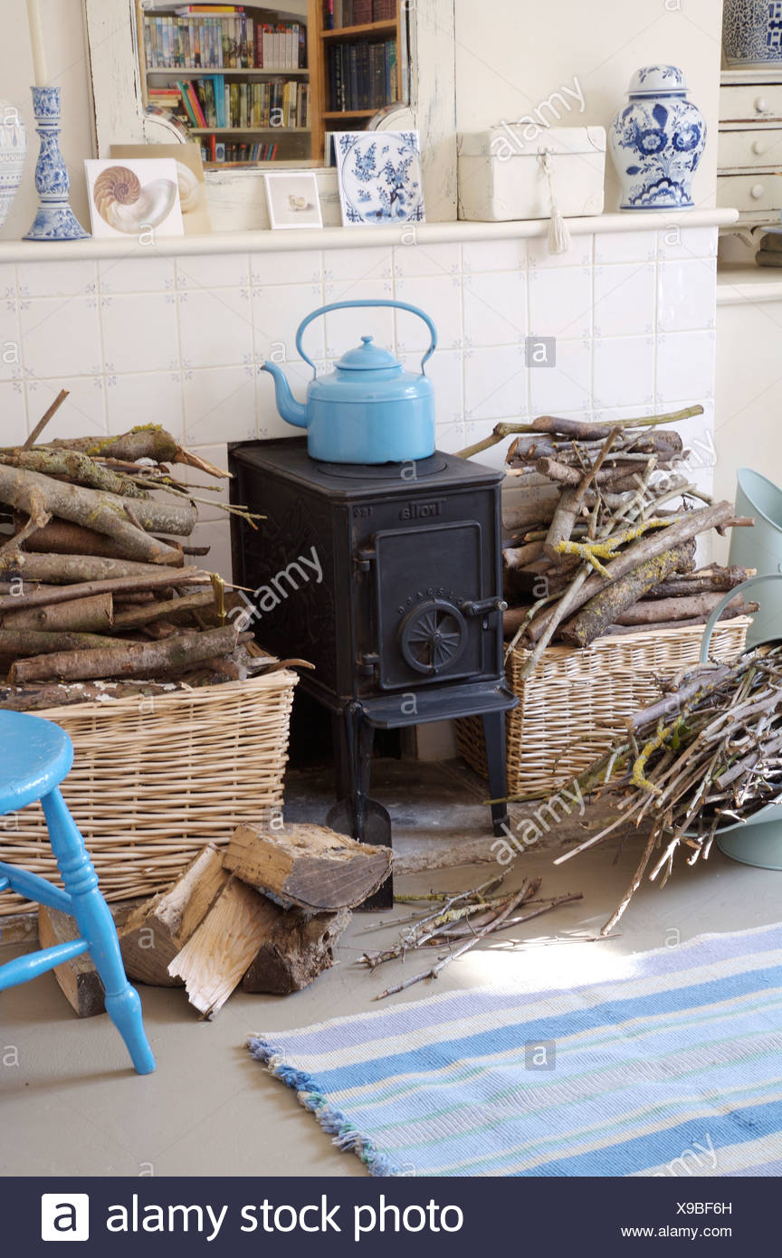 Blue Enamel Kettle On Small Black Wood Burning Stove In Dining Room Fireplace With Piles Of Kindling Baskets