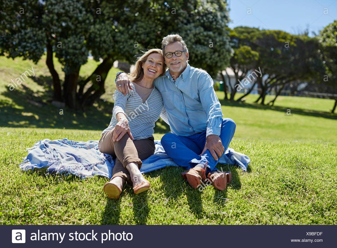 MODEL RELEASED. Senior couple on picnic blanket, arms around each other. - Stock Image