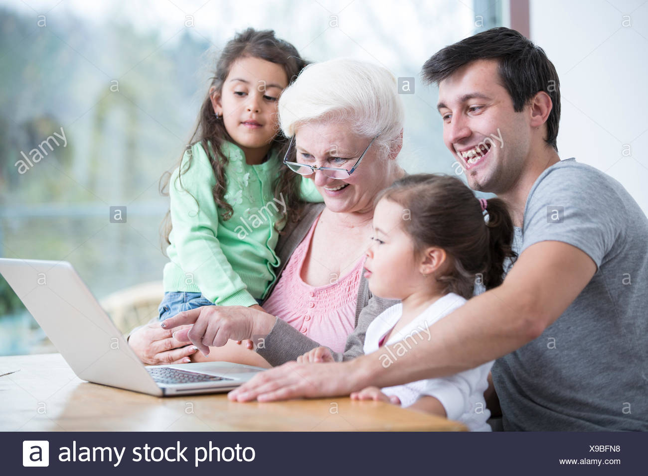 Happy three generation family using laptop at table in house - Stock Image