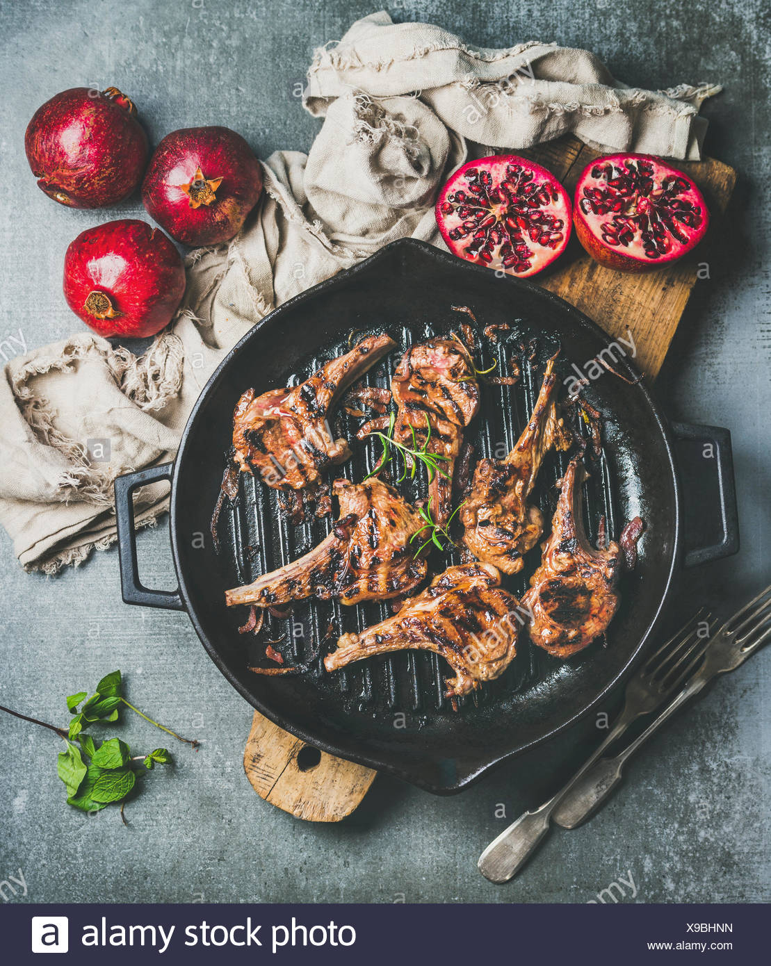Barbecue dinner. Grilled lamb meat chops with onion and rosemary in black cast iron pan served with fresh pomegranates on wooden board over grey concr - Stock Image