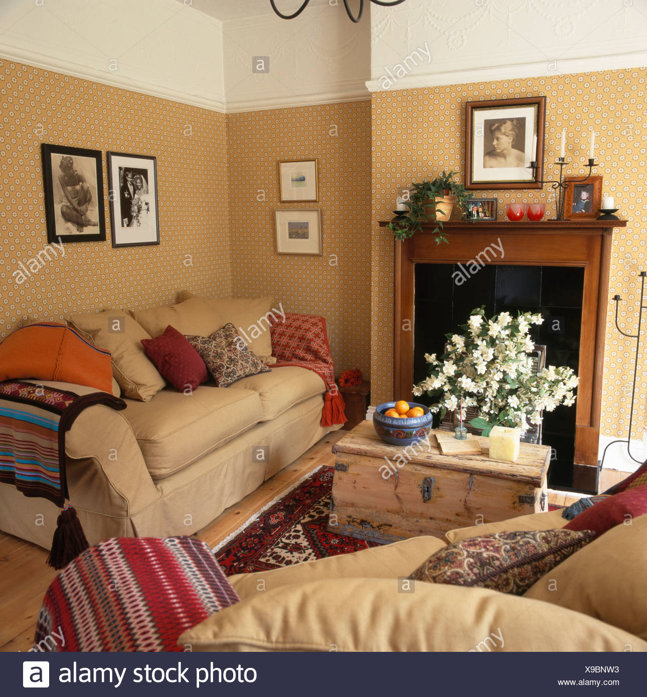 Pine chest in front of fireplace in livingroom with cream sofas and white cornice above patterned beige wallpaper