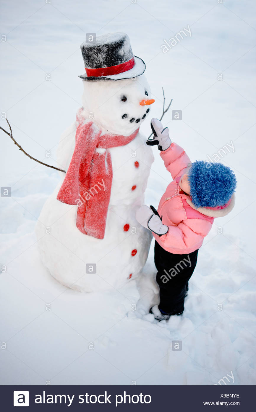 Young girl decorates a snowman with red scarf and black top hat, Alaska Stock Photo