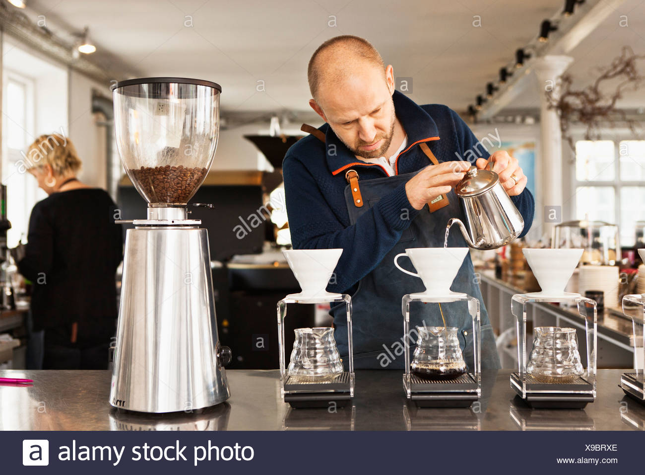 Barista pouring boiling water into coffee filters - Stock Image