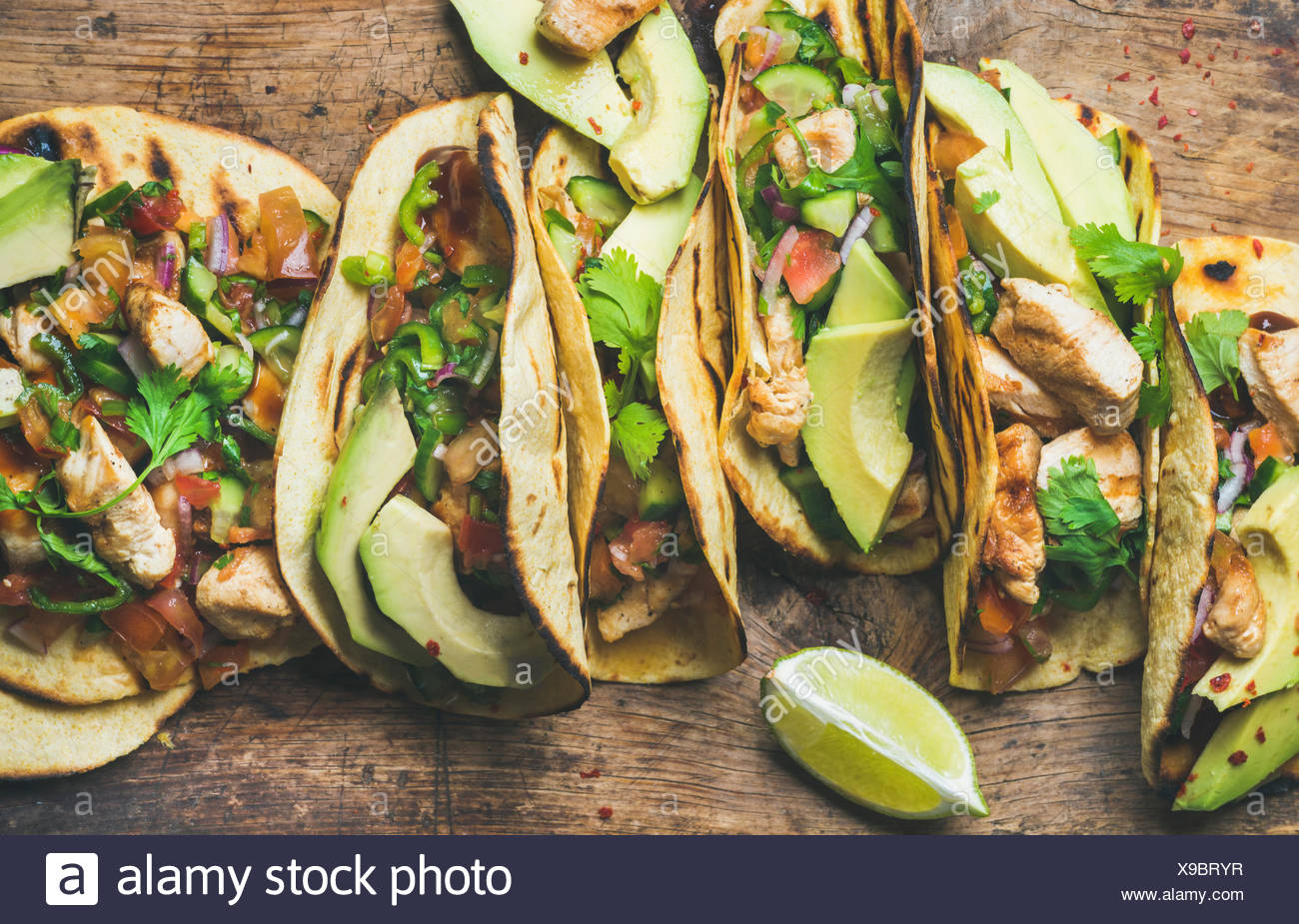 Tacos with grilled chicken, avocado, fresh salsa sauce and limes over rustic wooden background, top view. Healthy low carb and low fat lunch or food f - Stock Image