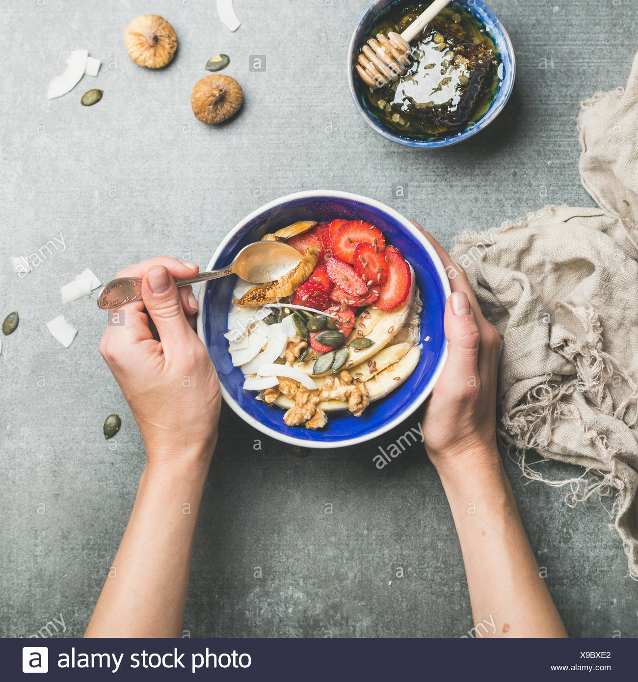 Yogurt, granola, seeds, fresh and dry fruit and honey in blue ceramic bowl in woman' s hands over grey concrete background, top view, square crop. Cle - Stock Image