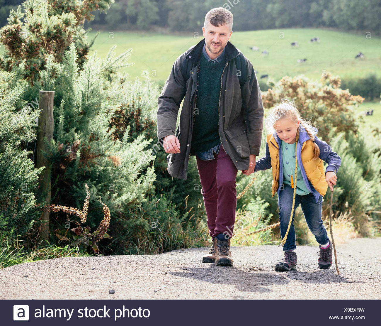 Father and daughter hiking up rural road - Stock Image