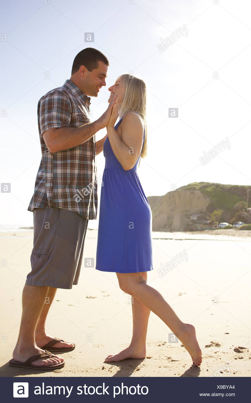 Couple touch each others hands and lean in for a kiss at the beach. - Stock Image