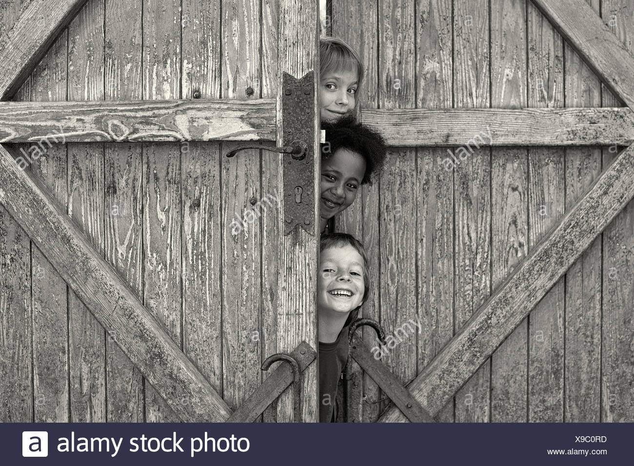 Three children looking out from behind door - Stock Image