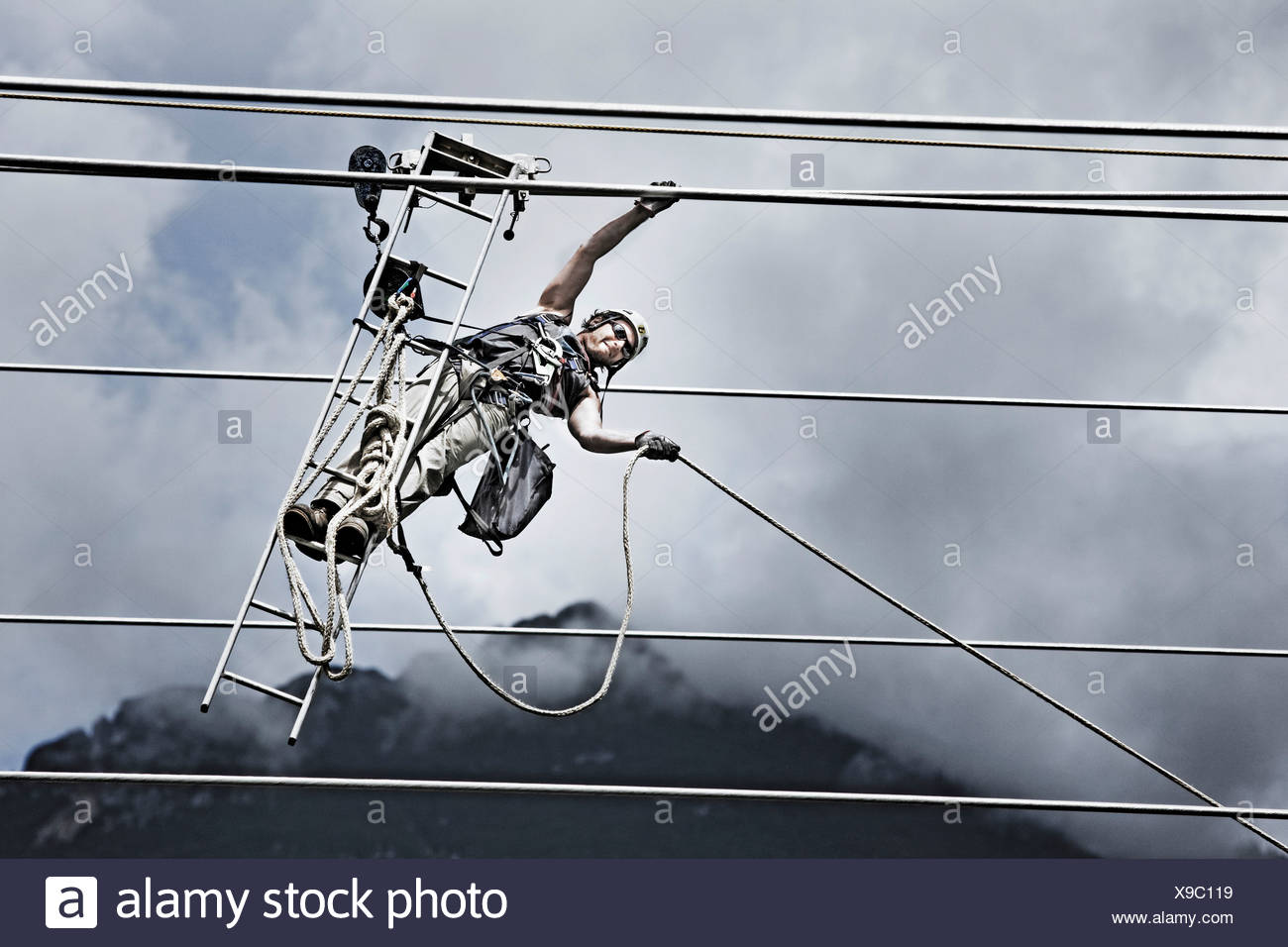 High-voltage service technician pulling a rope to get to the next pylon - Stock Image
