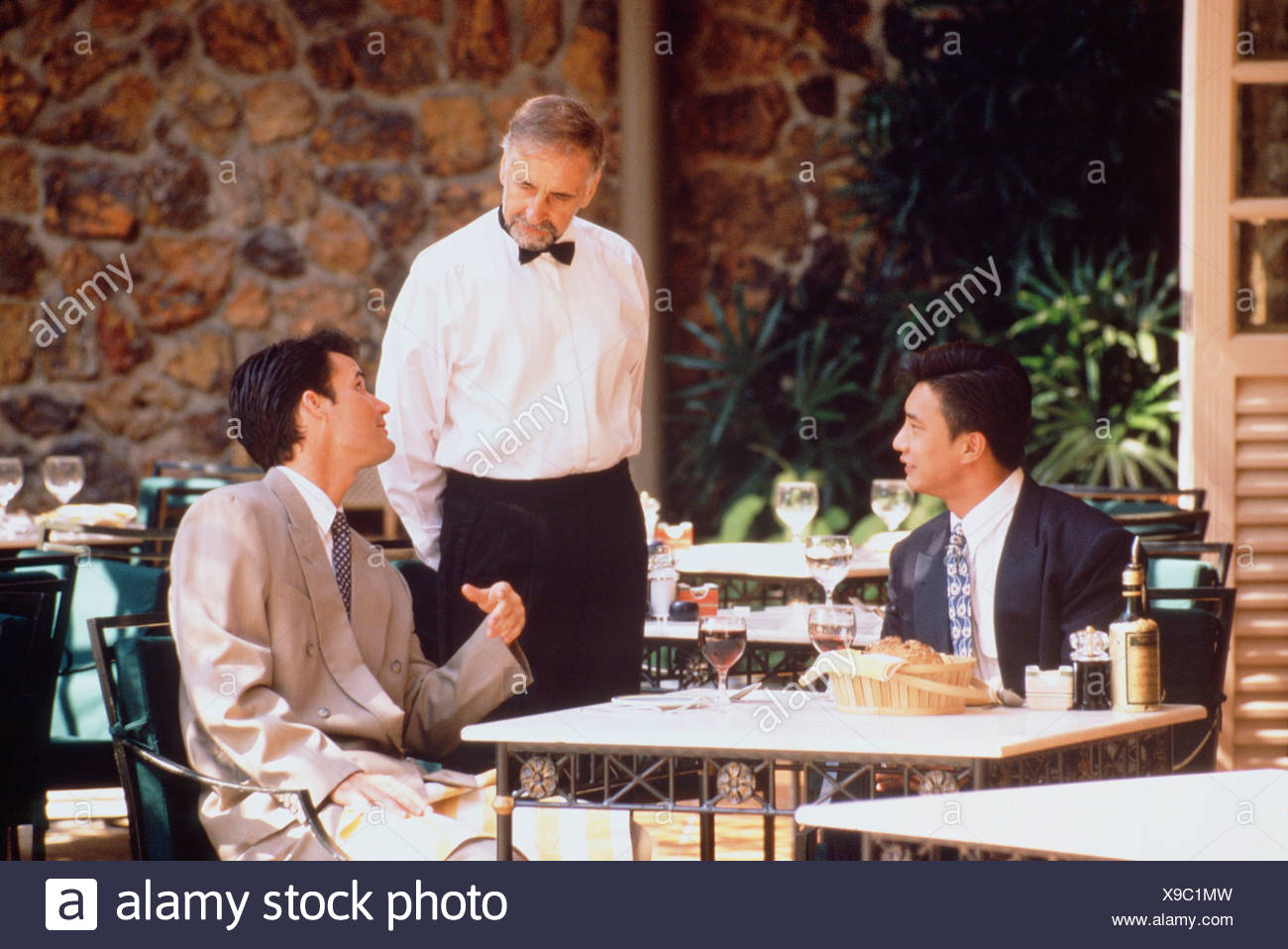 Two men seated at outdoor restaurant table conversing with waiter. Singapore. Stock Photo
