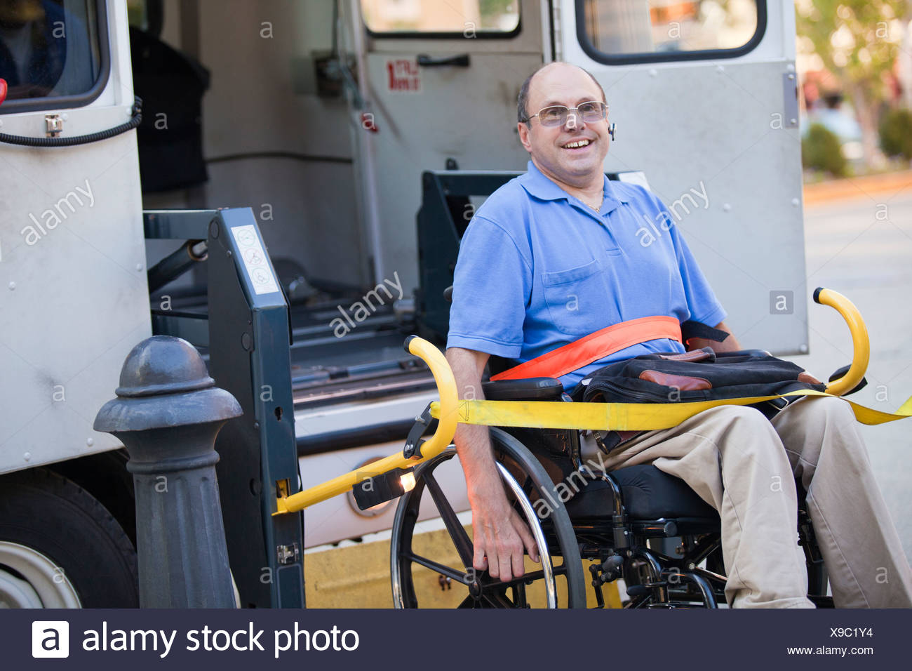 Man with Friedreich's Ataxia in a wheelchair entering accessible public transportation - Stock Image