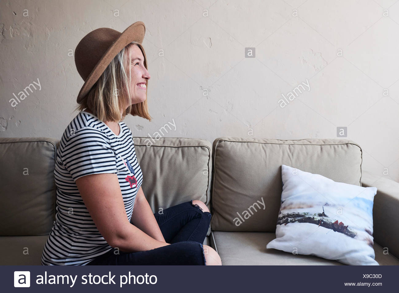 Woman sitting on sofa, smiling, side view - Stock Image