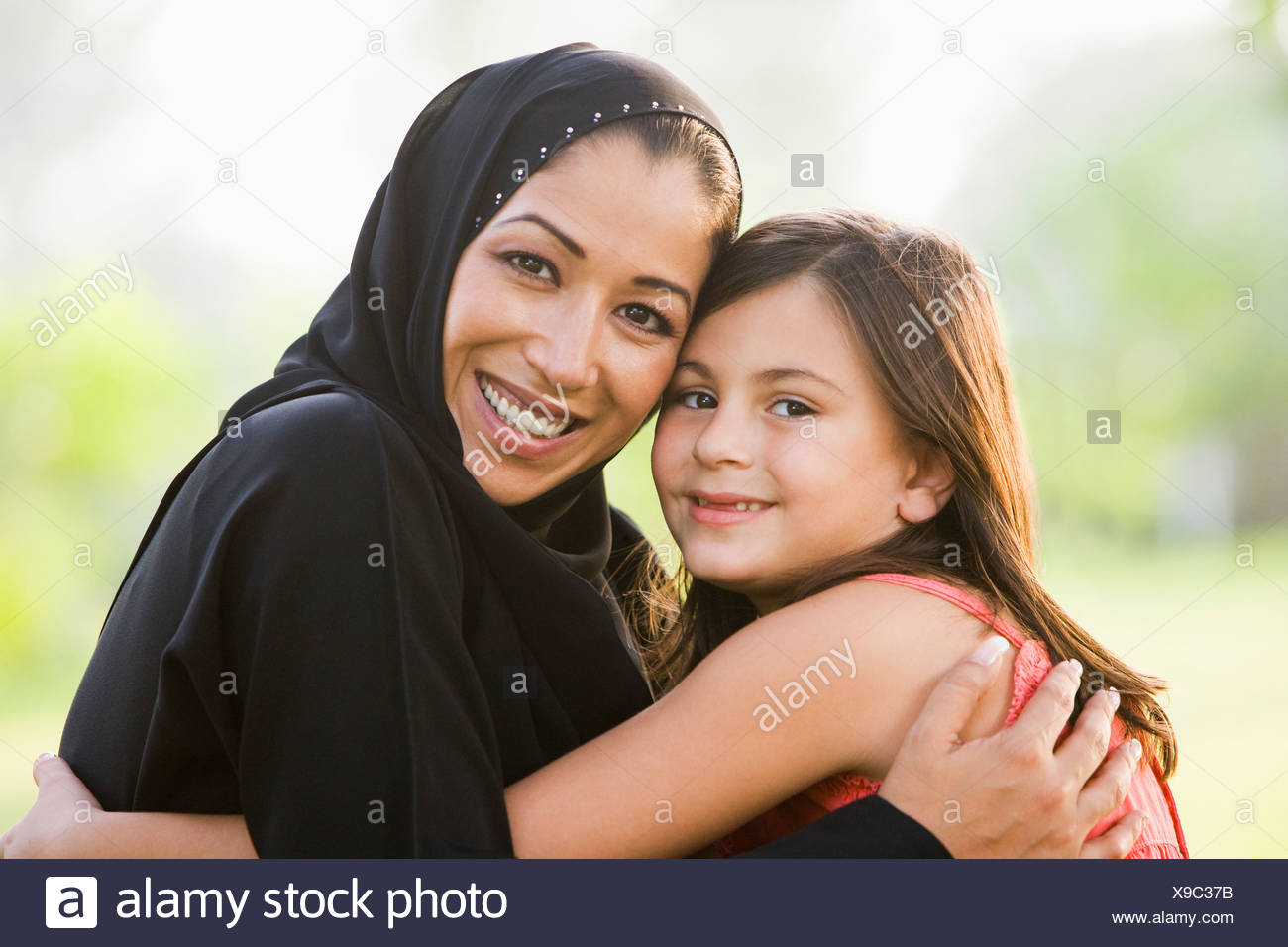 Mother and daughter outdoors in park embracing and smiling (selective focus) - Stock Image