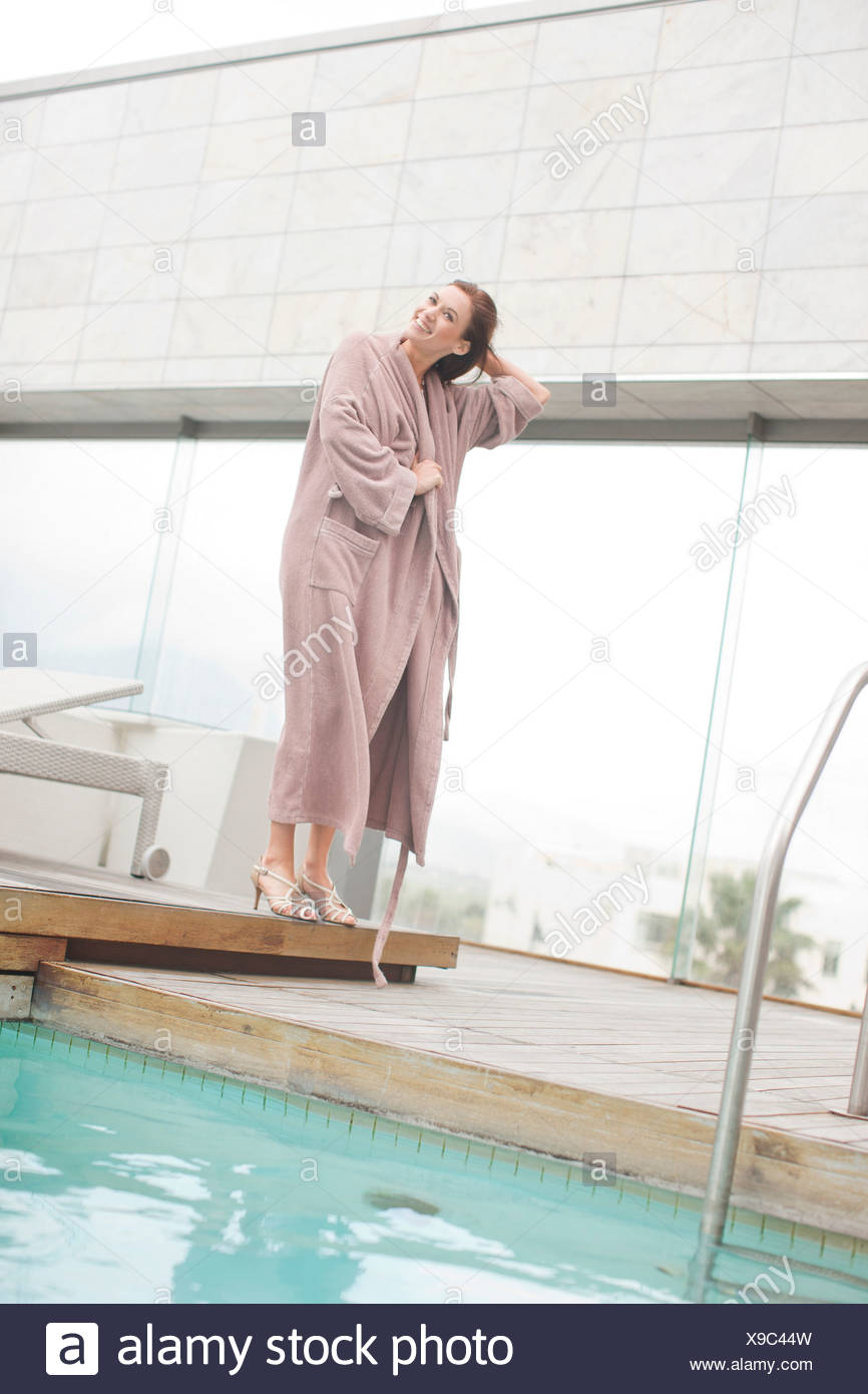 Woman wearing bathrobe at hotel poolside - Stock Image