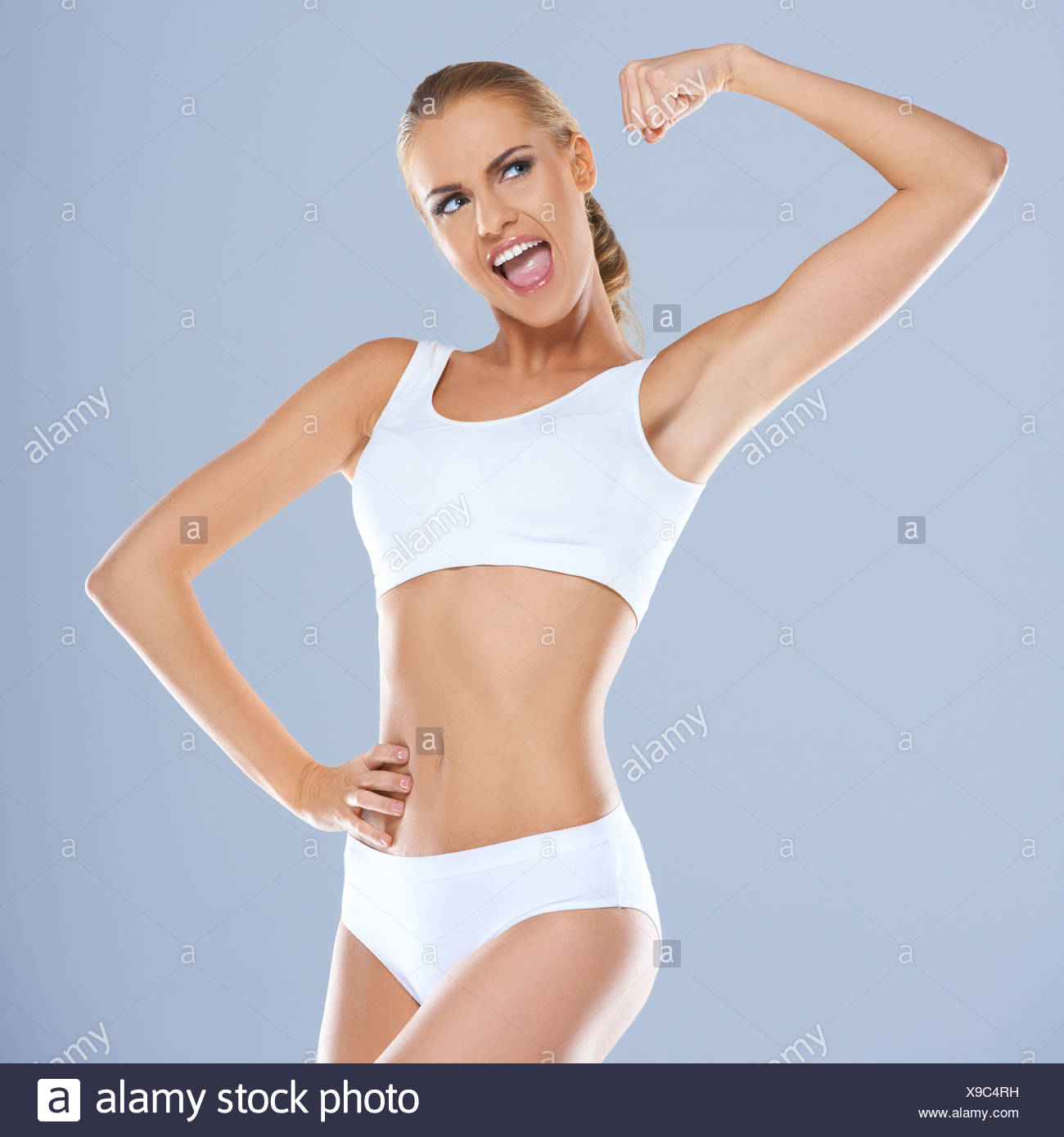 8f2d5ad2003 Portrait of young woman in white sportsbra smiling - Stock Image