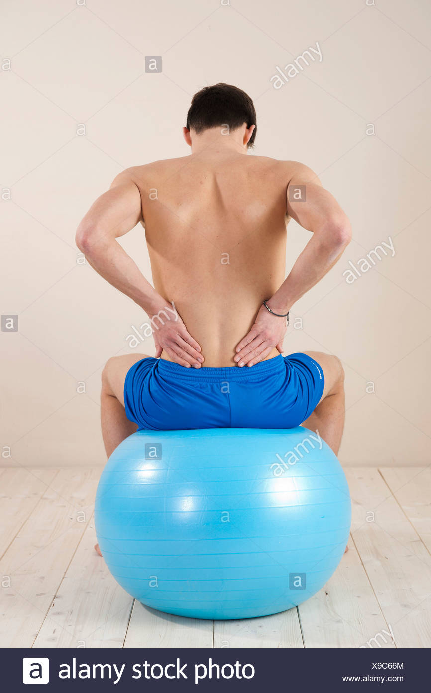 Young man sitting on a gym ball and touching his aching back - Stock Image