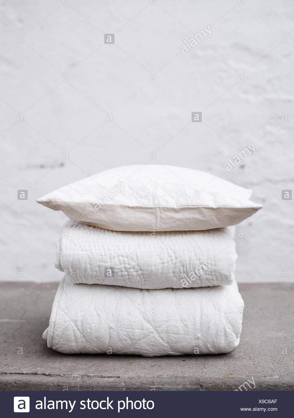 Scandinavia, Sweden, Stockholm, Folded blankets and quilt, close-up - Stock Image
