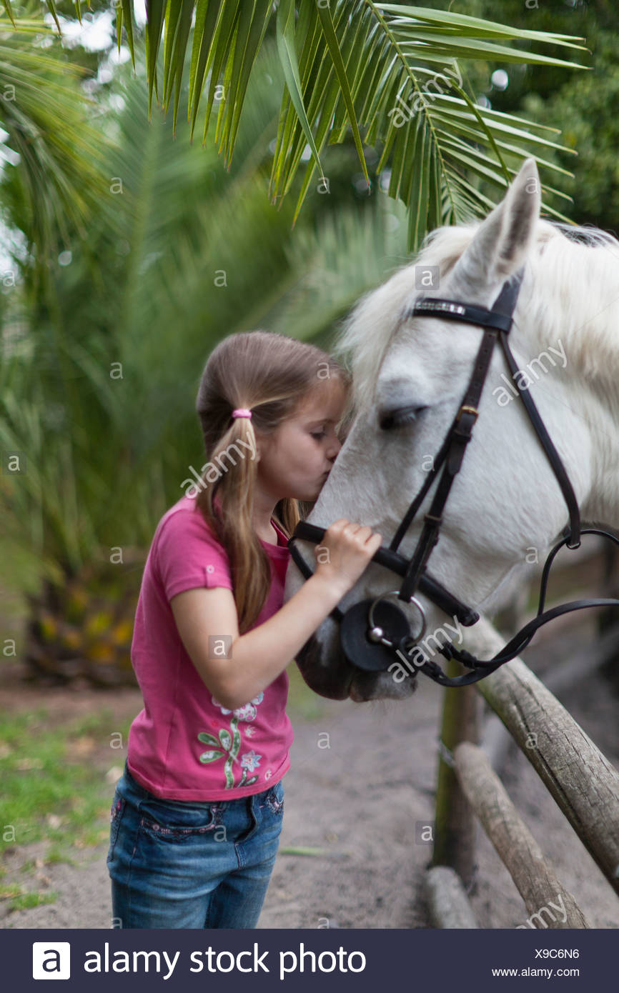 Girl kissing horse in yard - Stock Image