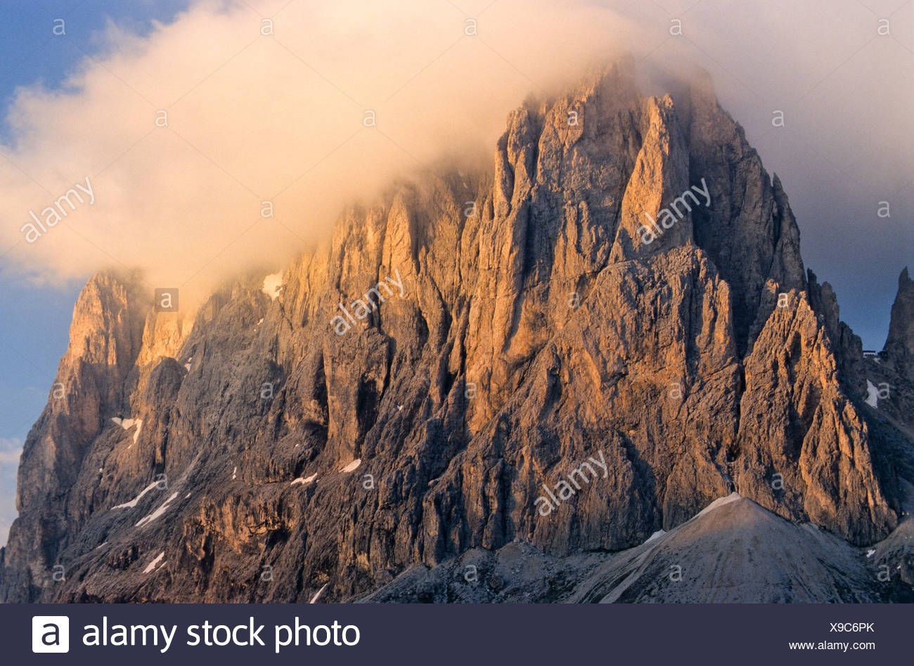Rock face of Mt. Langkofel, wispy clouds in pale evening light, Dolomites, Bolzano-Bozen, Italy, Europe - Stock Image