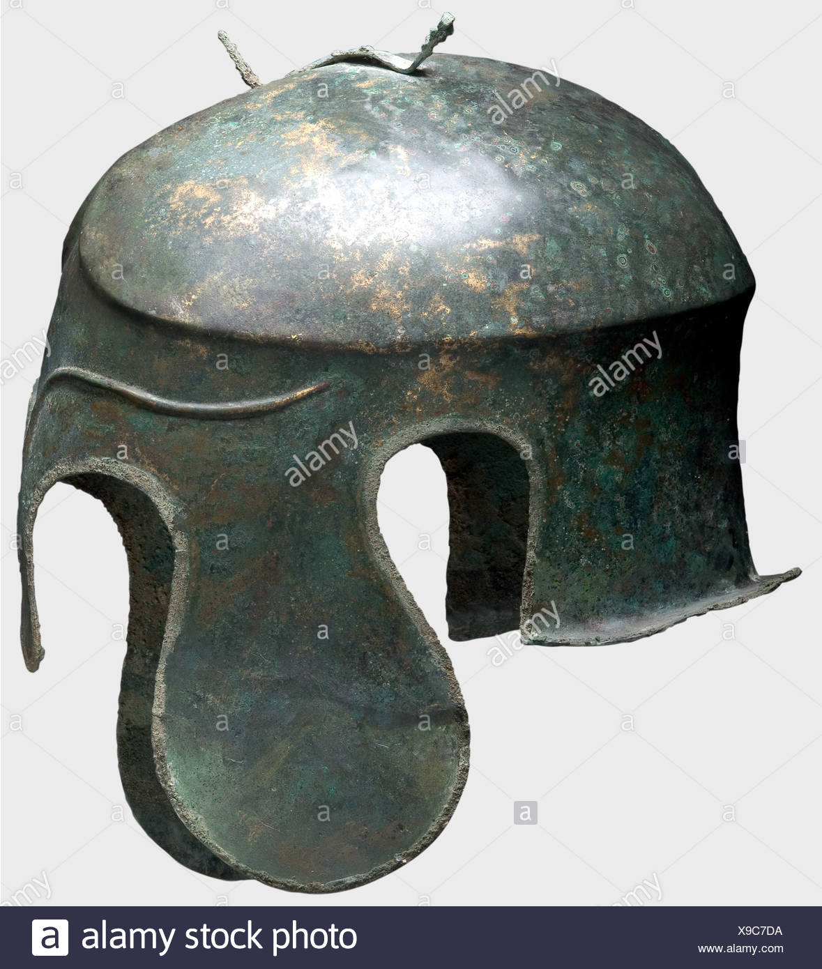 A Chalcidian helmet, 5th century B.C. Bronze. Narrow elongated skull with a carinated and crested crown, a fork-shaped attachment for the helmet plume, large lobed cheek pieces and ear cutouts, and a short flaring neck guard. The forehead with long decorative eyebrows in relief. The rim of the helmet has preserved some of the soldered edge moulding (solder in place all around). The left cheek piece is bent outward with severe nailing perforation, presumably from the votive offering of the helmet in a sanctuary. Height 19.5 cm. Weight 638 g. The metal is well-pr, Additional-Rights-Clearences-NA - Stock Image