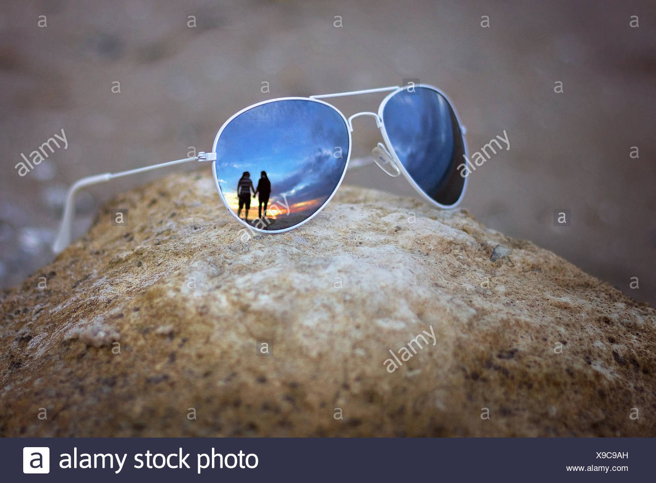 Reflection of couple in sunglasses - Stock Image